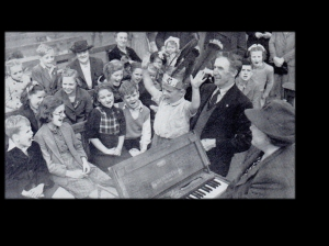 Seth and Bessie lead children to sing songs of the Savior. Note the small folding organ that Bessie is playing. Source: Eva Sykes Campbell, daughter of Seth and Bessie Sykes.