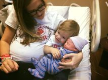 Rhory snuggles her newborn baby brother with an obviously happy Mom.